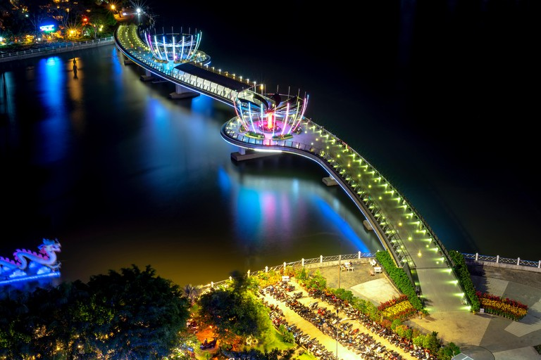 Colorful night walking bridge in Can Tho, Vietnam. This is Ninh Kieu wharf area along the waterway center in the Mekong Delta from the early 19th cent