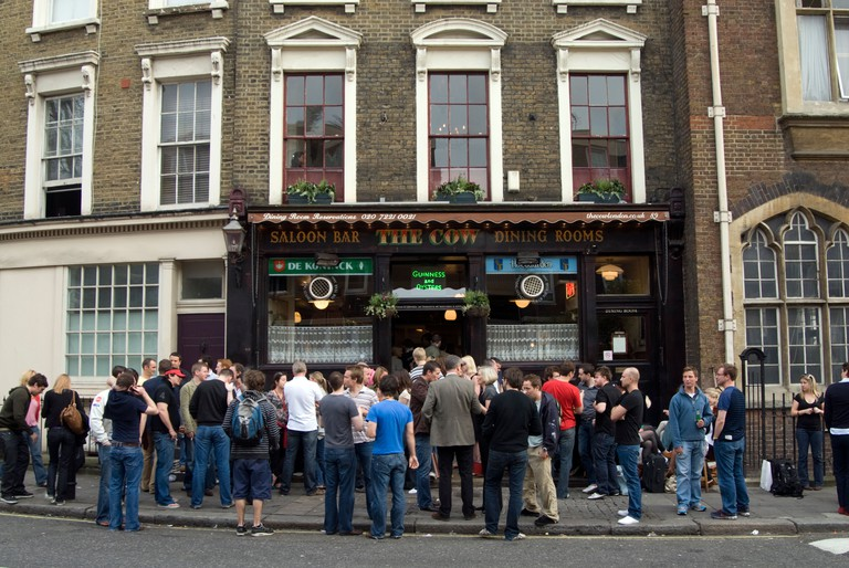 People drinking in the street outside The Cow pub in Westbourne Park Road, Notting Hill, London.