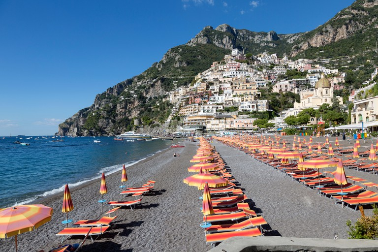 Colorful chair and umbrellas line the Spiaggia Grande beach, in Positano,Italy. Deep blue waters of the Tyrrhenian Sea.