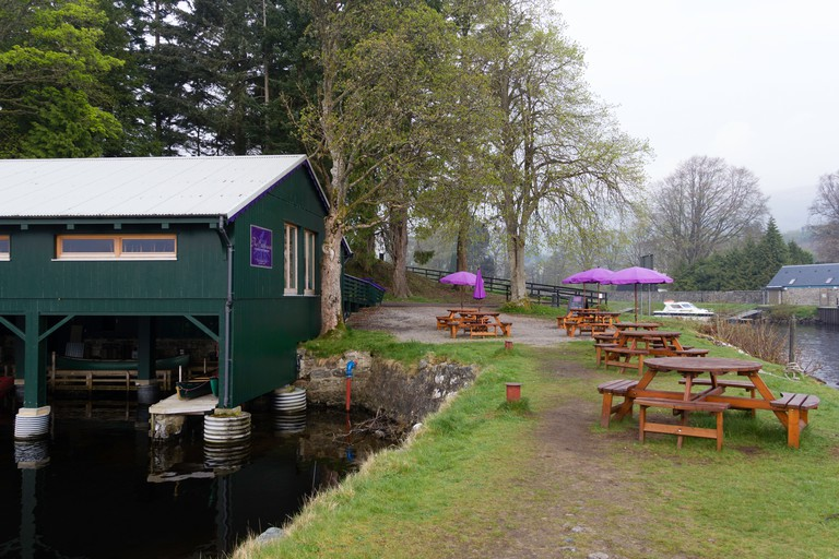 Boat yard and tables on the shore of Loch Ness in Scotland, part of a restaurant called Boathouse Restaurant in Fort Augustus