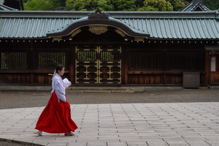 A shrine maiden crosses a courtyard at the Yasukuni Shrine in Kudanshita, Tokyo