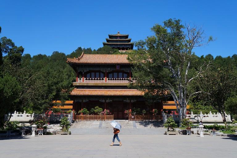 Woman walking past a building in Jingshan Park, Beijing, China