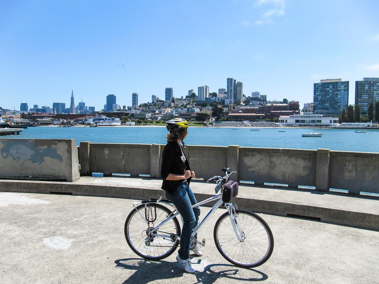 Woman on bicycle looking at skyline of San Francisco