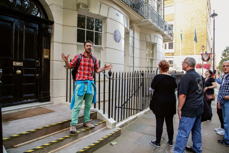 A tour guide outside John Lennon's house in London.