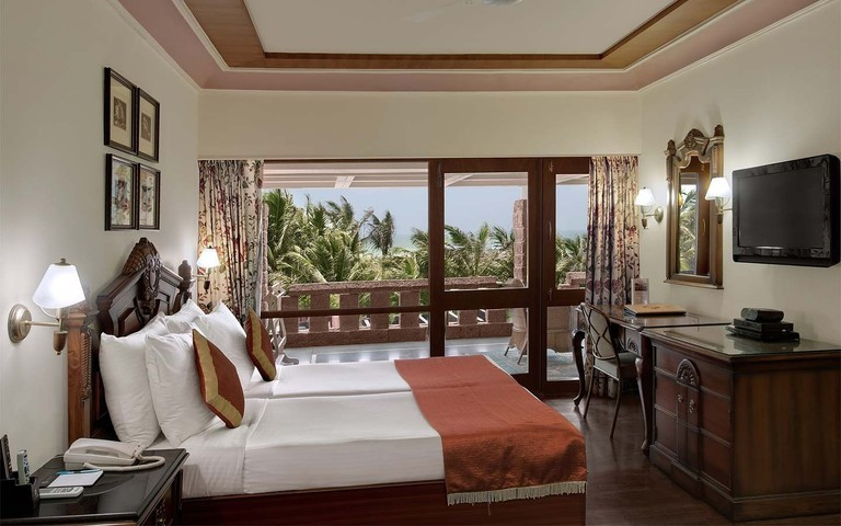 The bed, dark wood furnishings and balcony in a hotel room at MAYFAIR Heritage, Puri