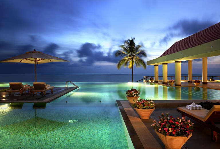 The pool looking out to the ocean in the evening at the Raviz Kovalam