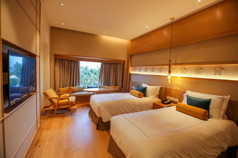 Two beds and a seating area at a hotel room in Taj Fisherman's Cove Resort & Spa, Chennai