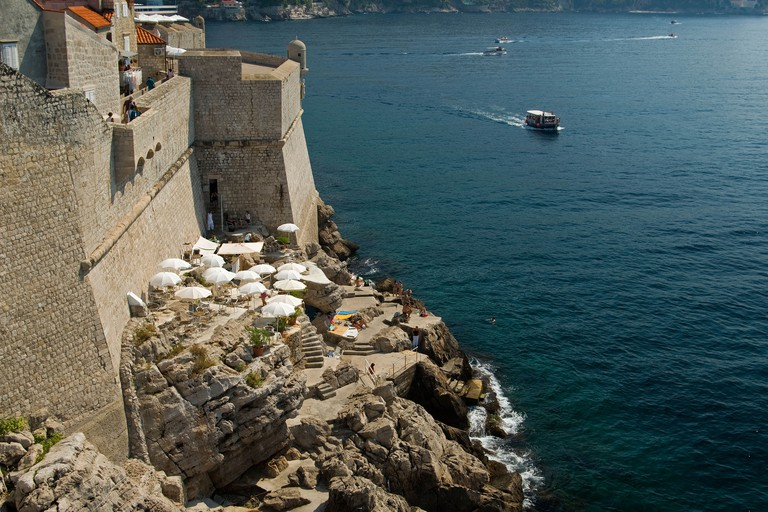 Croatia; Hrvartska; Kroatien; Dubrovnik, Old town, harbor, Caf Buza with white umbrellas perches on rock outside city walls