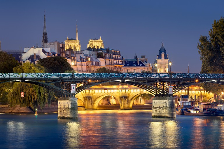 Pont des Arts, Pont Neuf, Notre Dame de Paris Cathedral towers and Seine River at night.