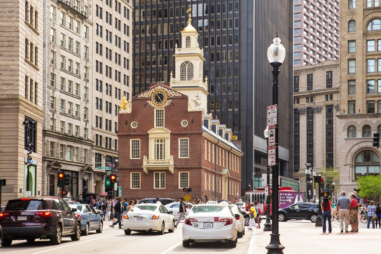 BOSTON, MASSACHUSETTS - MAY 14, 2016: Street view of historic Old State House along Boston's Freedom Trail, with cars visible.