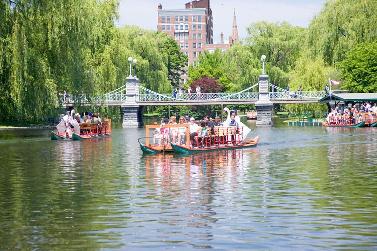 Swan Boat with tourists goes by Suspension Bridge in Public Garden and Boston Common in summer, Boston, Ma., New England, USA