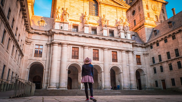 A young woman, tourist in a hat is standing in front of the basilica at El Escorial palace and monastery at the San Lorenzo de El Escorial at sunset