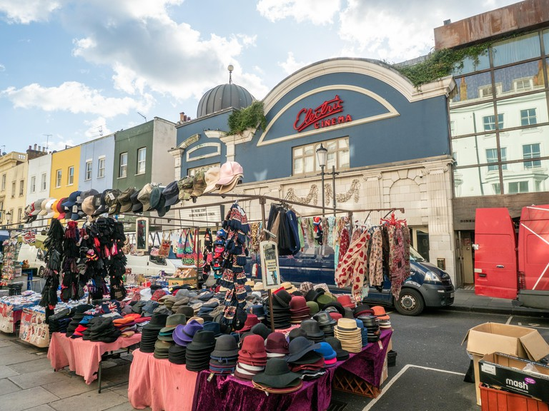 Hats for sale at a market on Portabello road, Notting Hill, London.Behind is the blue facade of Electric Cinema.