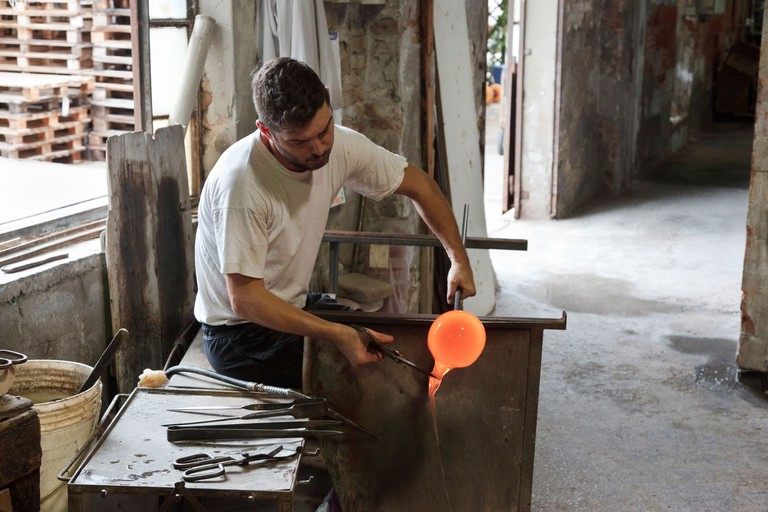 Man working with molten glass to create the famous Murano glass at a glass foundry on the island of Murano, Venice, Italy