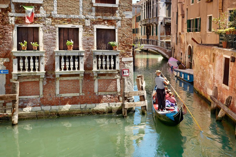 Gondolier flowing gondola, Venice canal, Veneto, Italy, UNESCO