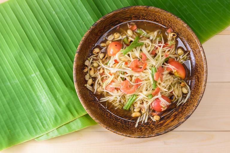 papaya salad (papaya pok pok) top view on a wooden table and green banana leaf, Thai local food.
