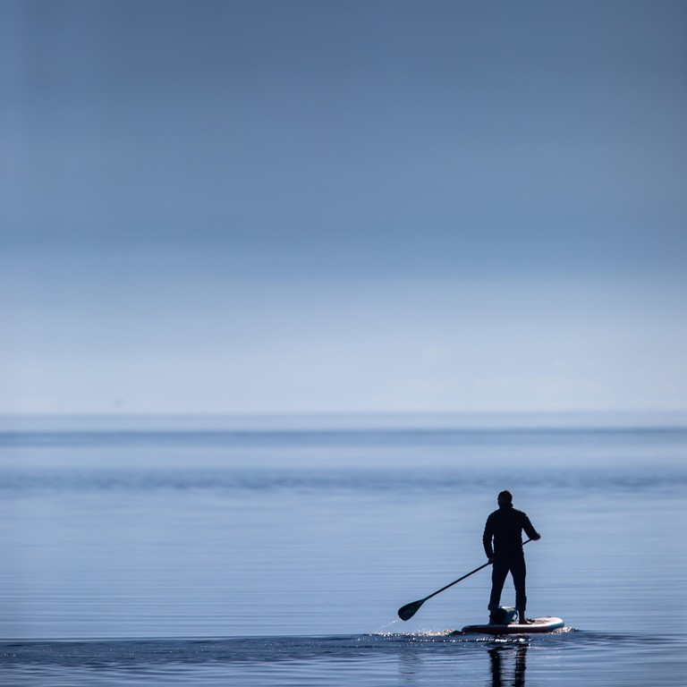 Man on a stand up padlle board on a lake