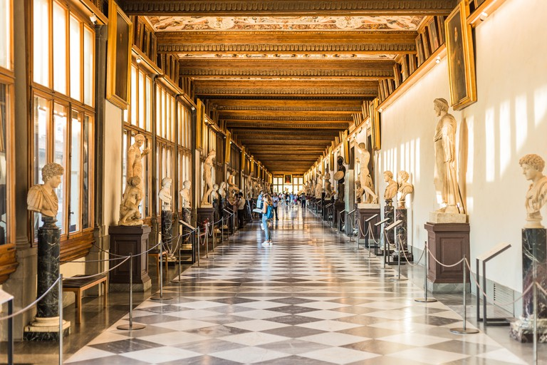 Florence, Italy - September 25, 2016: Tourists in hallway of Uffizi Gallery, one of the oldest and most famous art museums of Europe.