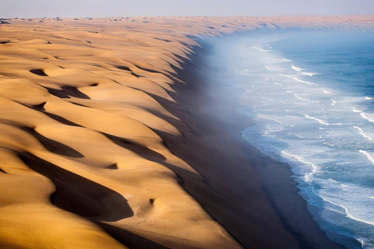 The waves of the Atlantic Ocean advance toward the sand dunes of the Namib Desert Namibia Africa