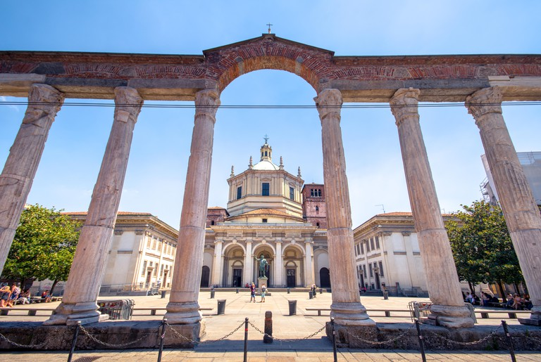 View of the Colonne di San Lorenzo, roman historical colonnade, with the statue of roman emperor Costantine, in Milan, Italy.