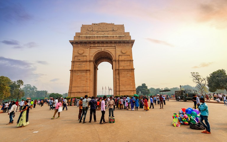 Tourists gather near India Gate in Delhi at sunset