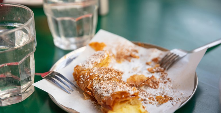 Bougatsa, greek traditional cream pastry served with sugar and cinnamon garnish
