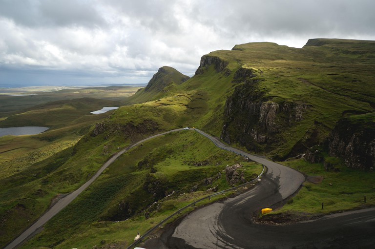 Long winding road at Quiraing on the Isle of Skye with a beautiful vibrant scottish sky.