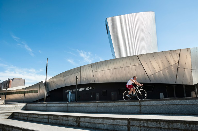 Cyclist riding past the Imperial War Museum North, Manchester, UK