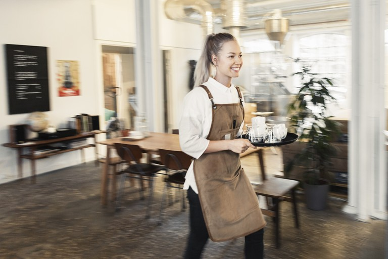Happy female worker holding tray while walking at cafe