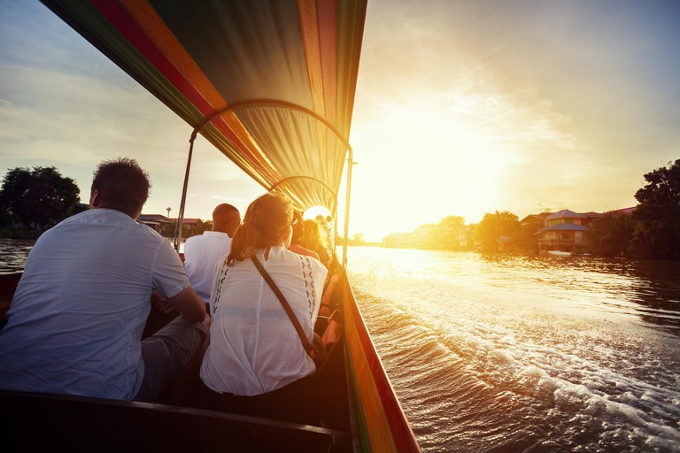 Tourist sitting in long-tail boat cruise by Chao Phraya river