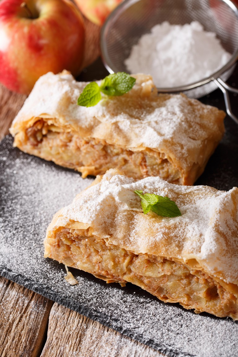 Apple strudel sprinkled with sugar powder close-up on the table. Vertical