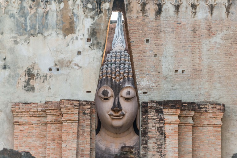 Buddha image in ruined church of temple in Sukhothai historical park, travel destination of Thailand