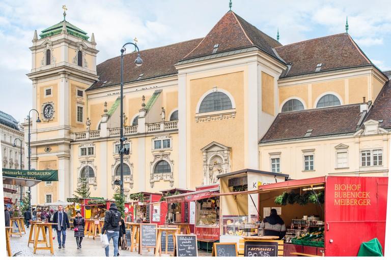 The Freyung Christmas market with Schottenkirche Catholic Church to the rear, Vienna city centre, Austria.