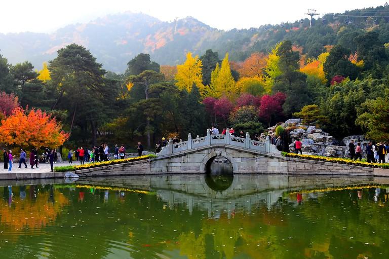 People walk on a bridge in Xiangshan Park in Beijing