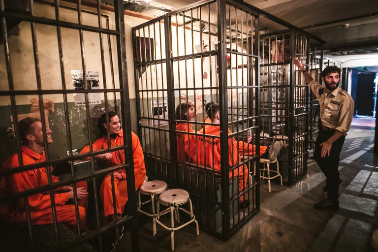 Don a bright orange prison jumpsuit behind bars while you wait for the prison guards to bring the drinks