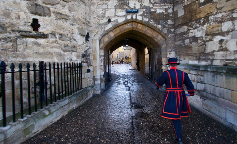 A Yeoman Warder walks beneath Byward Tower at the Tower of London in London England