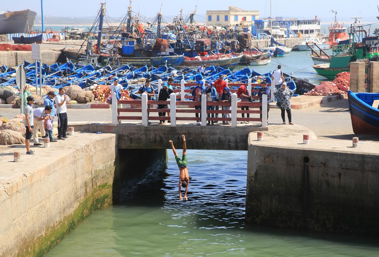 Local boys playing in the harbour, diving off the bridge, in Essaouira, Morocco, North Africa