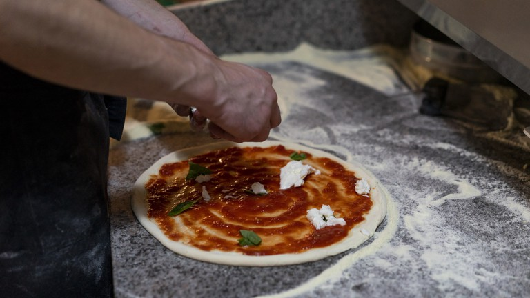 Close-up of pizza baker preparing a pizza with tomato sauce and mozzarella in kitchen