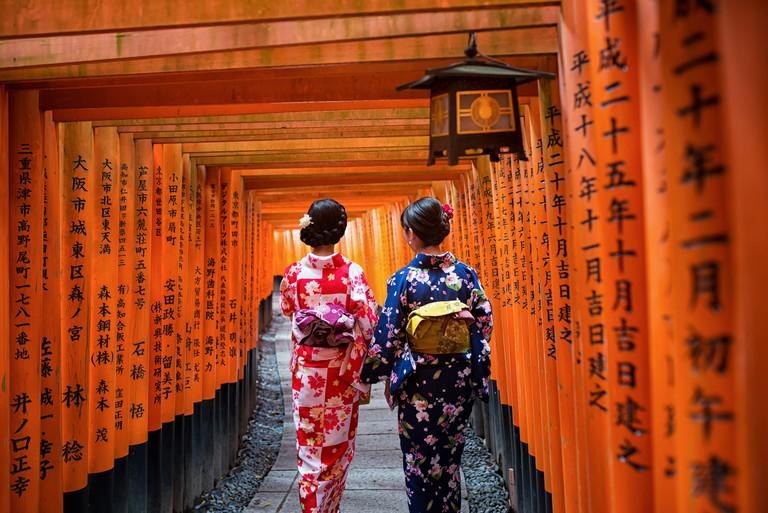 Two geishas wearing traditional japanese kimono among red wooden Tori Gate at Fushimi Inari Shrine in Kyoto, Japan. Fushimi Inari Shrine one of famous landmarks.