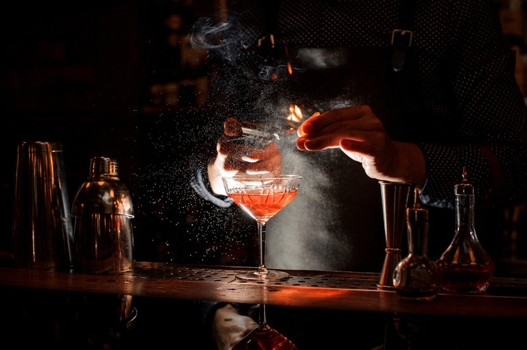 Bartender setting fire to sweet cocktail in bocal