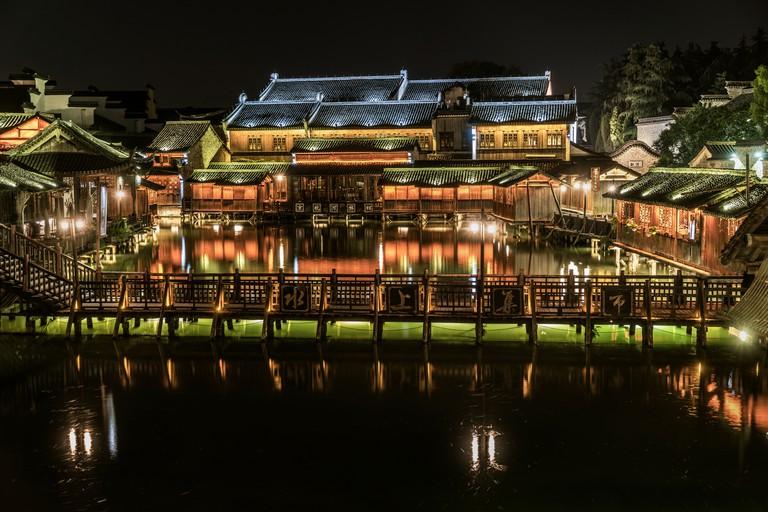 Illuminated bridge and traditional houses in Wuzhen Water Town, Wuzhen, Zhejiang, China