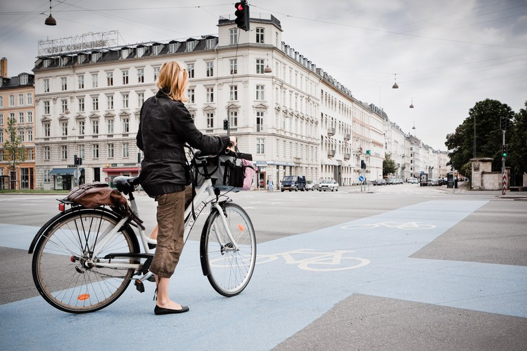 Crossroads in Copenhagen Denmark as a cyclist waits to cross. Denmark is a cycle friendly nation with an extensive network of cycle routes nationwide.
