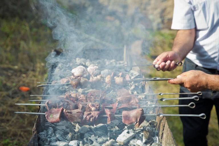 Appetizing lula kebab grilled on metal skewer. Hand and swallow kebab swab. Shish kebab on a metal stick, top view. Lula kebab on skewers