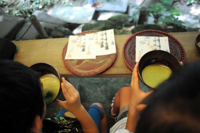 VIsitors have a cup of matcha green tea at Hokoku-ji, (bamboo temple)