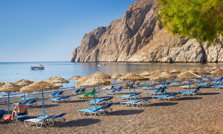 Beach chairs and sun umbrellas at Kamari Beach (southeastern part of the Santorini), Santorini Island, Greece