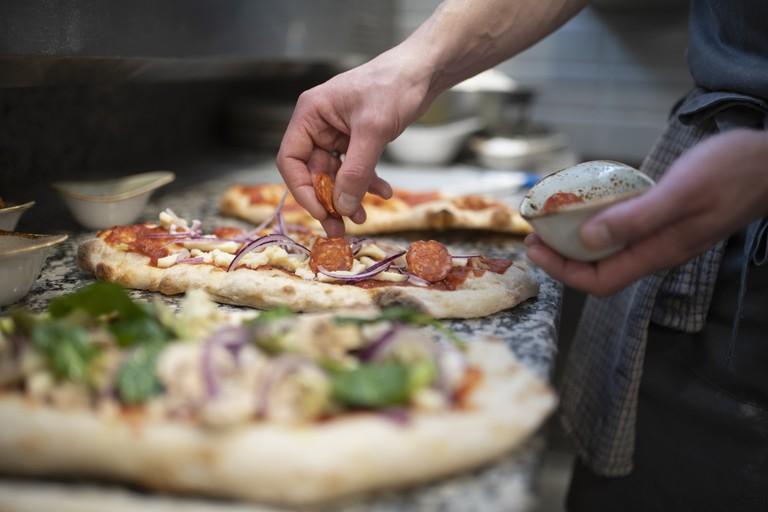 Chef placing sausage onto Pinsa Romana base, a Roman style pizza blend