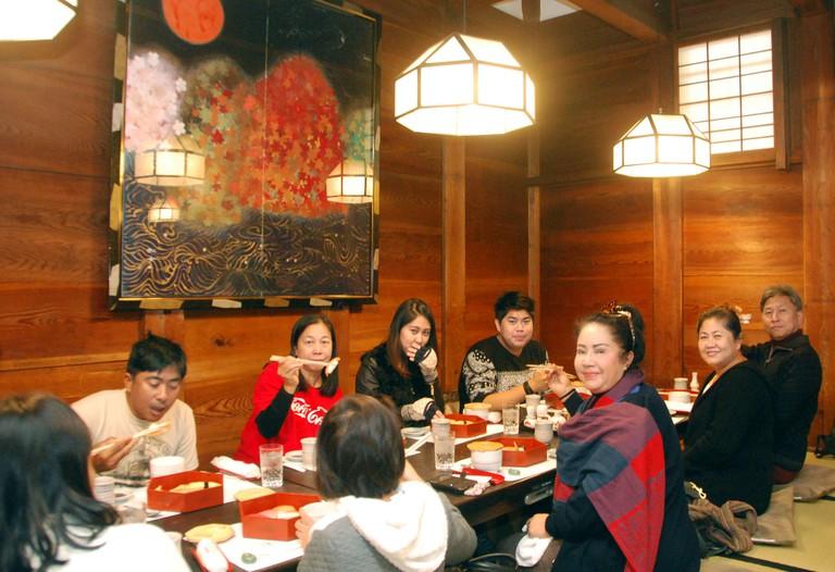 Tourists enjoy sushi at Ganko restaurant, Kyoto, Japan.