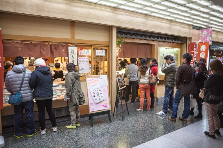 Visitors stand in queue to entrance of Japanese restaurant the Sushi no Musashi.