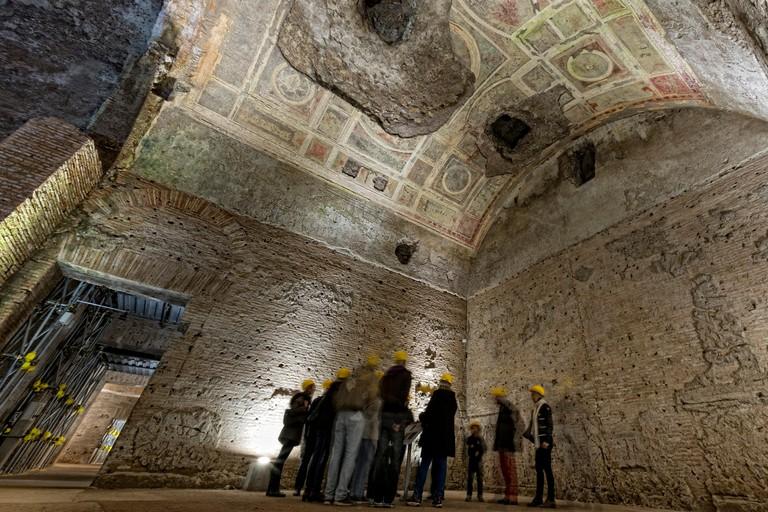 people exploring antique roman ruins being restored