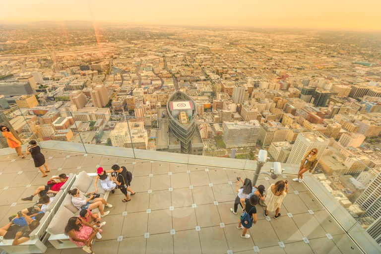 Los Angeles, California, United States - August 9, 2018: aerial view of tourists taking photo on panoramic terrace at twilight. People looking at LA Downtown skyline from Oue Skyspace U.S. Bank Tower.